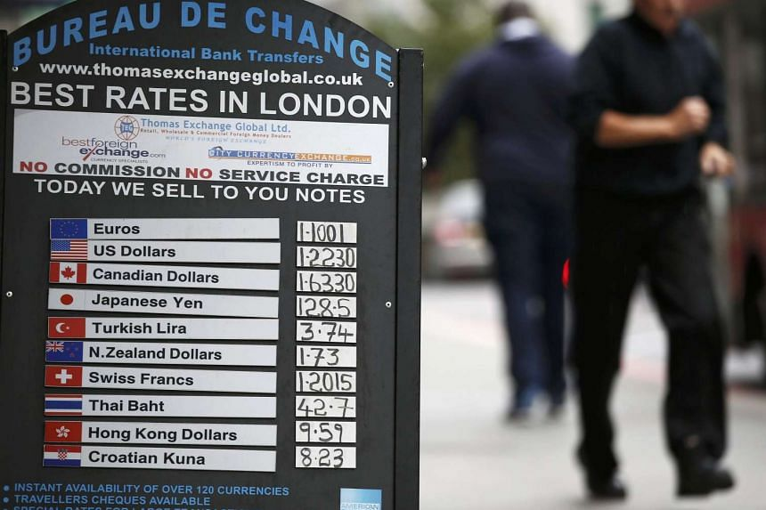 A money changer advertises rates on a board in London on Oct 7, 2016.