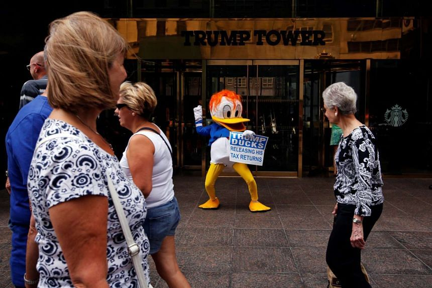 An activist with a sign referring to US presidential candidate Donald Trump and his tax returns outside Trump Tower in New York City last month. Based on the few pages of Mr Trump's 1995 tax returns that have become public, the writers have concluded that