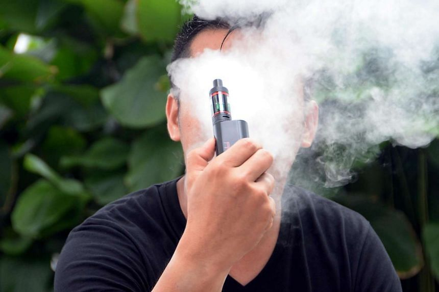 A posed picture of a man smoking an e-cigarette.