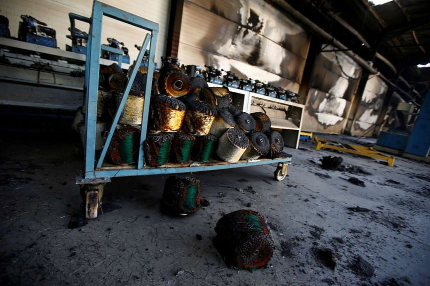 Torched bundles of woven fabric are seen in a textile factory damaged by protests in the town of Sebeta, Oromia region, Ethiopia on Oct 8, 2016.