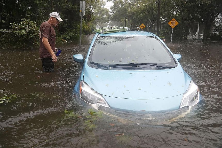 A car sitting in a flooded street in St Augustine, Florida, as Hurricane Matthew passed through the area on Friday. As of 8am yesterday, the National Hurricane Centre had downgraded Matthew to a Category 1 hurricane with maximum sustained winds of 13