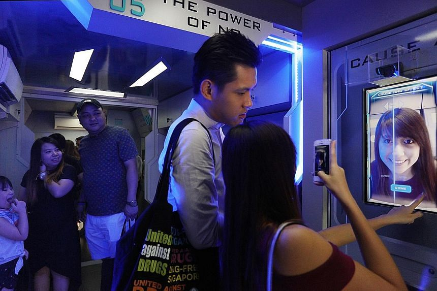 """Visitors on board the """"Drug Buster Academy Bus"""" at CNB's one-day roadshow at VivoCity yesterday. This special bus makes use of augmented reality technology to transform people's faces so they can see for themselves what drugs can do to them."""