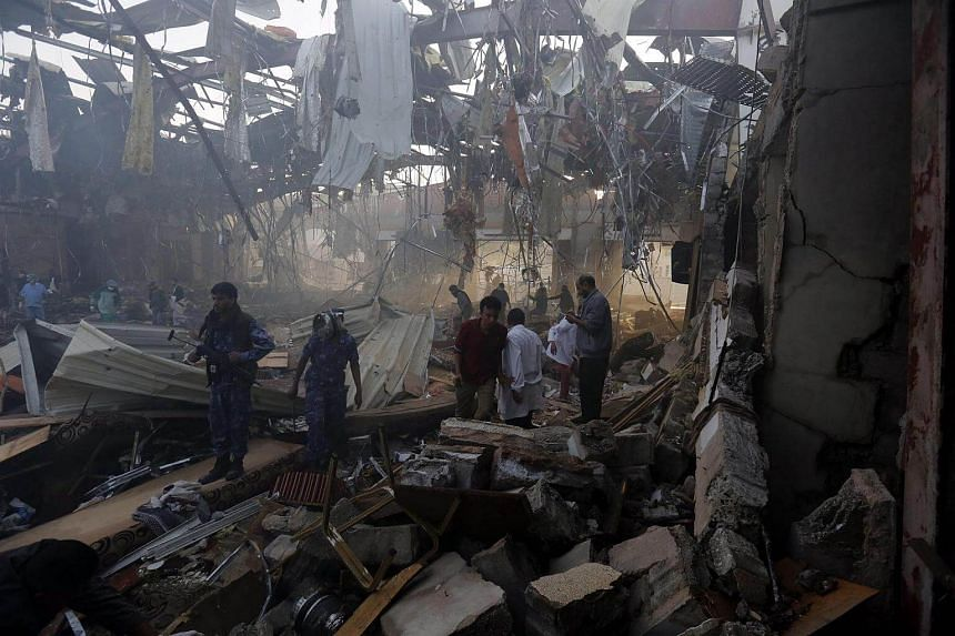 Yemenis inspect the site of Saudi-led airstrikes hit a funeral ceremony in Sana'a, Yemen on Oct 8, 2016.
