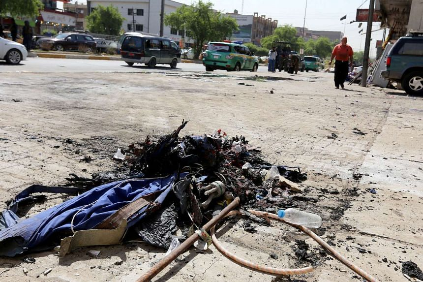 Debris from an explosion are seen after a Shi'ite procession was targeted by a bombing, in Baghdad, on Oct 9, 2016.