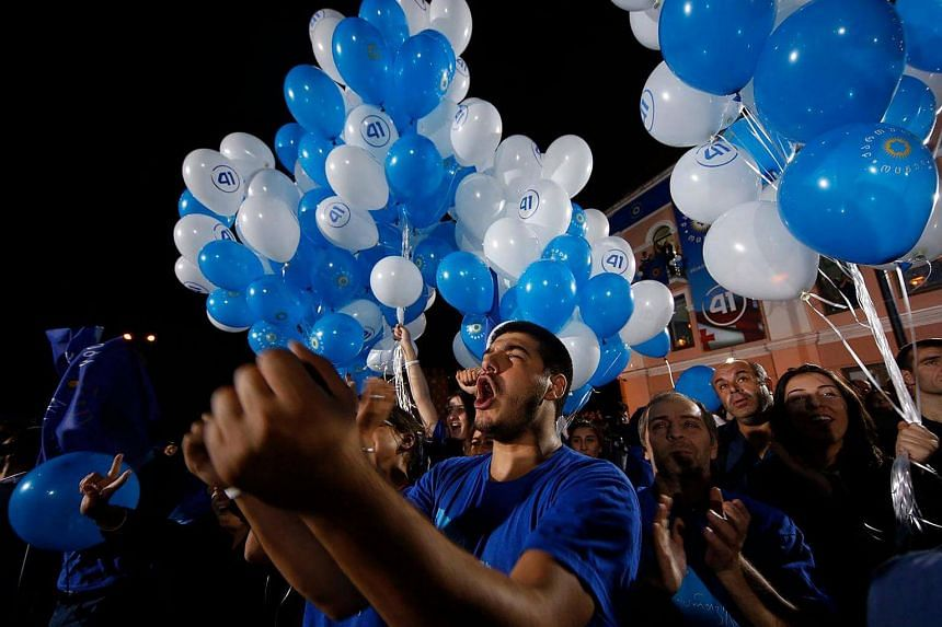Georgian Dream party supporters cheer, wave flags and hold up balloons during a rally after the parliamentary elections in Tbilisi on Oct 8, 2016.