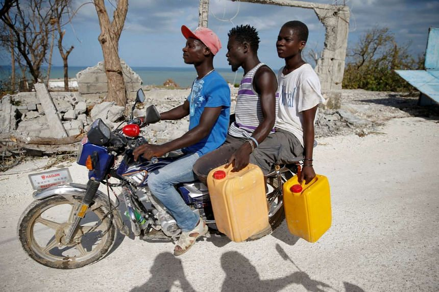 Men ride a motorcycle in front of destroyed houses after Hurricane Matthew passes Jeremie, Haiti, on Oct 7, 2016.
