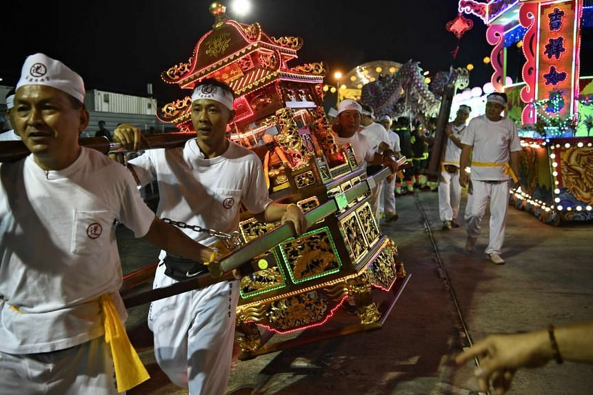 Taoist devotees holding a sedan as it sways, signifying the arrival of the Nine Emperor Gods during the festival at Pulau Punggol Timor on Sept 30, 2016.