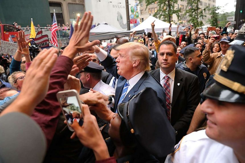 US Republican presidential candidate Donald Trump greets supporters outside Trump Towers in Manhattan on Oct 8. 2016.