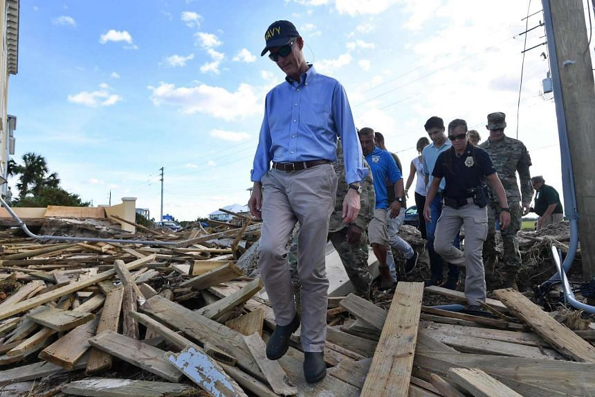 Florida governor Rick Scott (centre) walks over debris as he visits a damaged beach in St Augustine, Florida, on Oct 8, 2016.