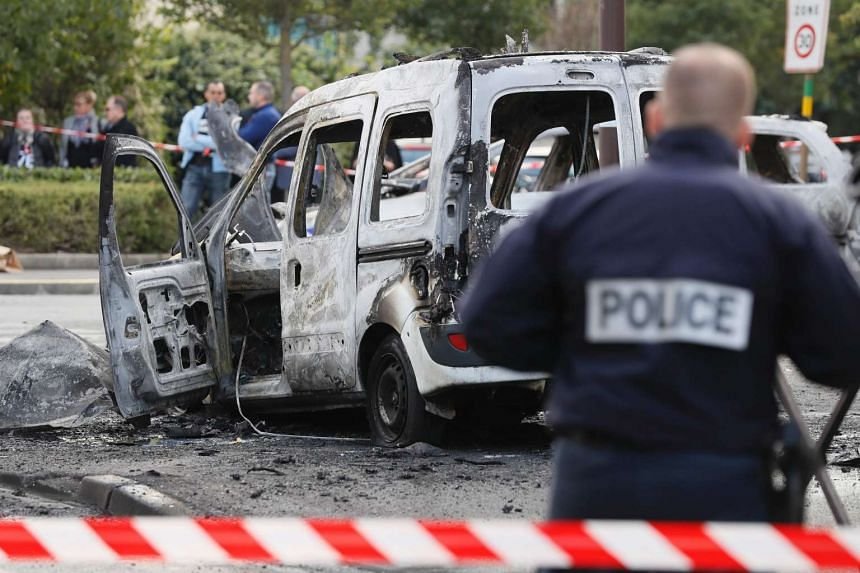 A police officer stands guard near a burned police vehicle and van after the Molotov cocktail attack.