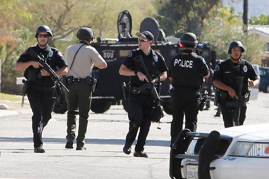 Armed police officers at the standoff where three officers were shot by a suspect.