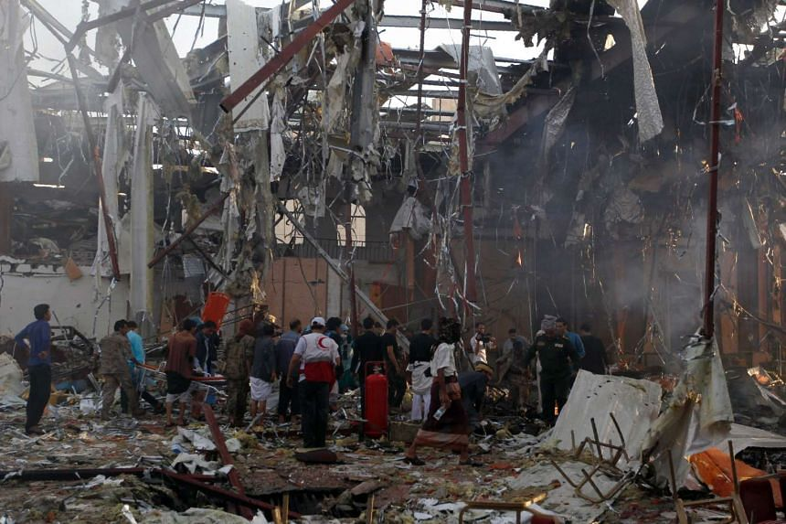 A picture taken on Oct 8, 2016, shows Yemenis and rescue teams gather at the site of reported airstrikes by Saudi-led coalition air-planes in the capital Sanaa.