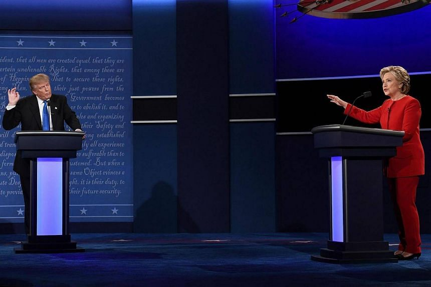 Republican nominee Donald Trump (left) looks on as Democratic nominee Hillary Clinton speaks during the first presidential debate on Sept 26, 2016.