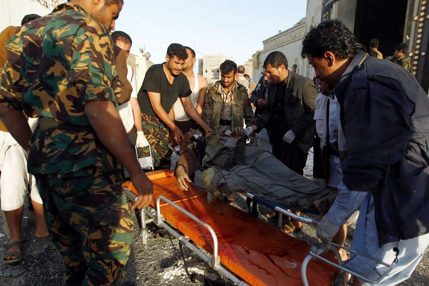 Yemeni rescue workers carry a victim amid the rubble of a destroyed building following reported airstrikes by Saudi-led coalition air-planes on the capital Sanaa on Oct 8, 2016.