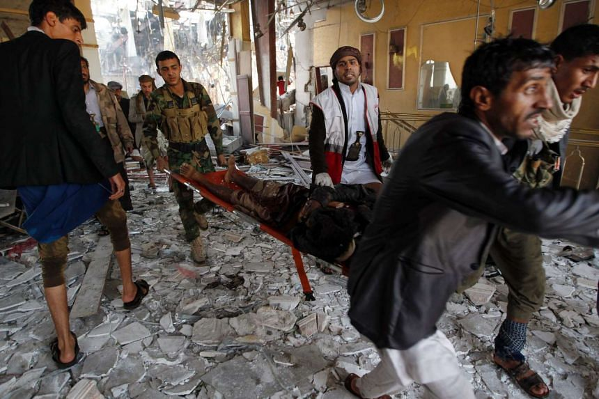 Yemeni rescue workers carry a victim on a stretcher amid the rubble of a destroyed building following reported airstrikes by Saudi-led coalition air-planes on the capital Sanaa on Oct 8, 2016.