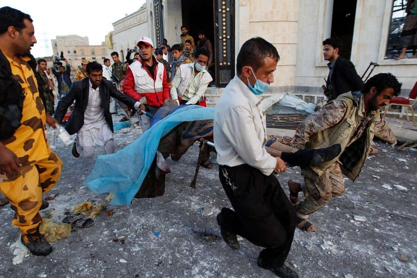 Yemeni rescue workers carry a body amid the rubble of a destroyed building following reported airstrikes by Saudi-led coalition air-planes on the capital Sanaa on Oct 8, 2016.