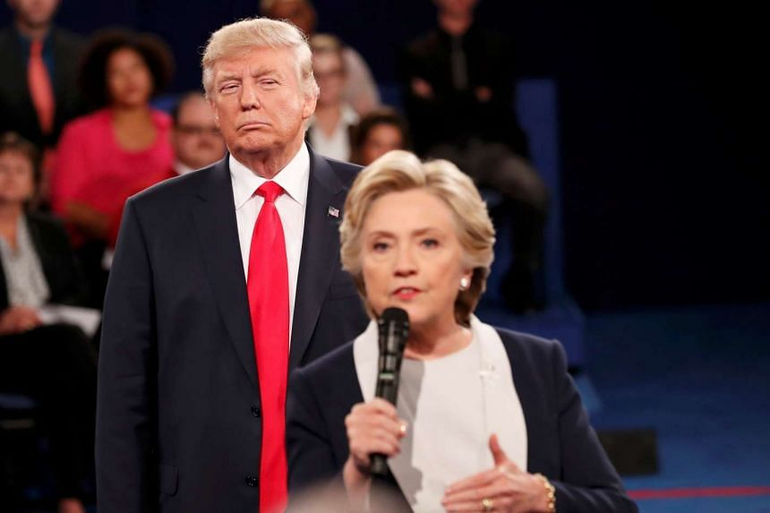 Donald Trump listens as Hillary Clinton answers a question from the audience during their presidential town hall debate at Washington University on Oct 9, 2016.