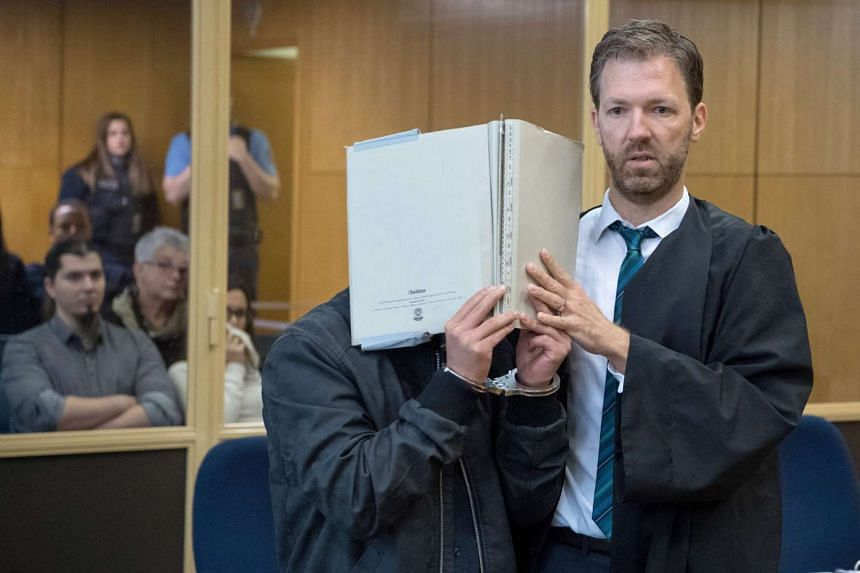 A lawyer representing Yejun G (face covered), one of the defendants in a murder case, guides his client into the courtroom in Frankfurt, Germany, on Oct 10, 2016.