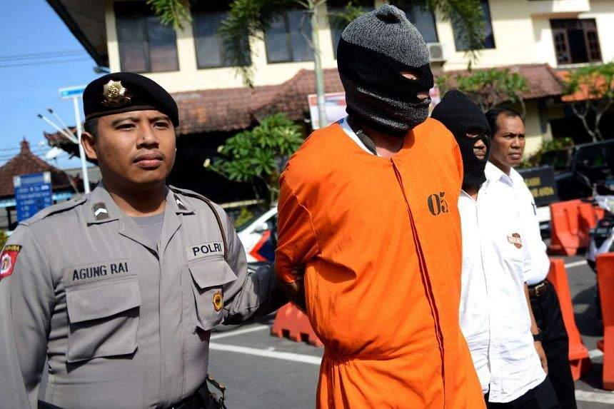 David Fox is escorted by police to a press conference at a police station in Denpasar on Bali island on Oct 10, 2016.