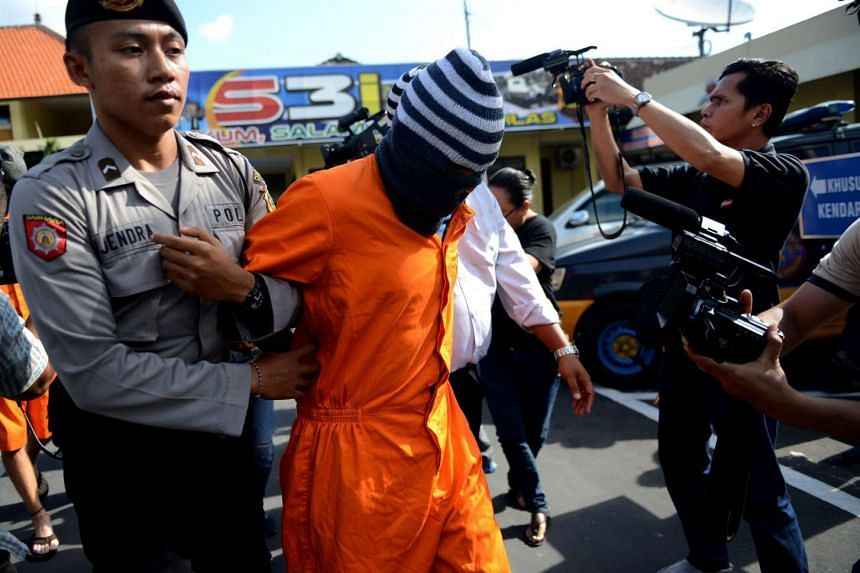 Giuseppe Serafino is escorted by police to a press conference at a police station in Denpasar on Bali island on Oct 10, 2016.