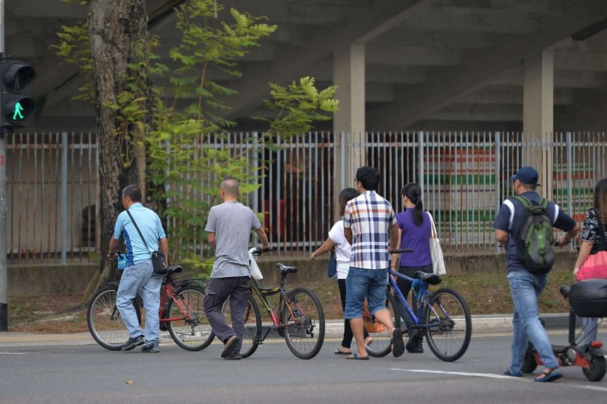 Cyclists pushing their bicycles across the road.
