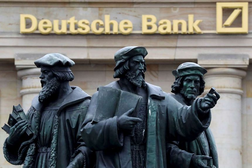 A statue is pictured next to the logo of Germany's Deutsche Bank in Frankfurt, Germany.