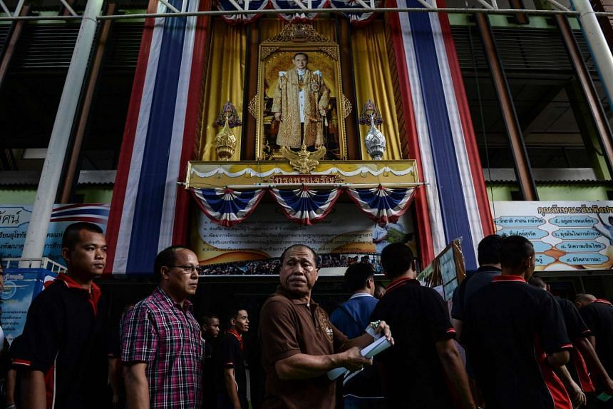 A portrait of Thai King Bhumibol Adulyadej (centre, top) is seen as people queue to vote at a local polling station during the constitutional referendum in Bangkok on Aug 7, 2016.