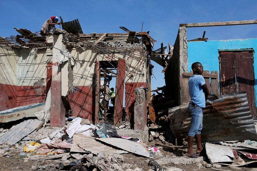 Men salvage metal sheets from a destroyed house after Hurricane Matthew passes in Jeremie, Haiti, on Oct 8, 2016.