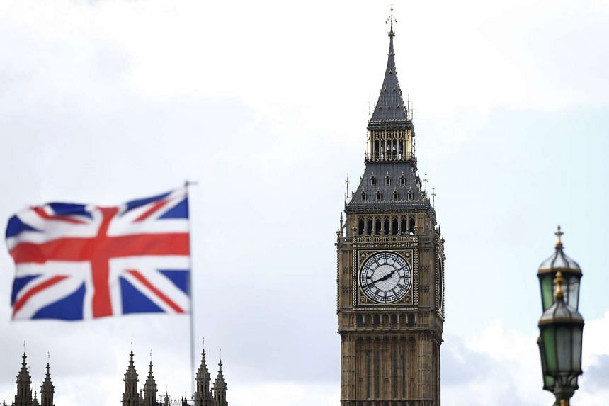 A Union flag on sale at a souvenir stall flies in the breeze opposite the Houses of Parliament in London, Britain.