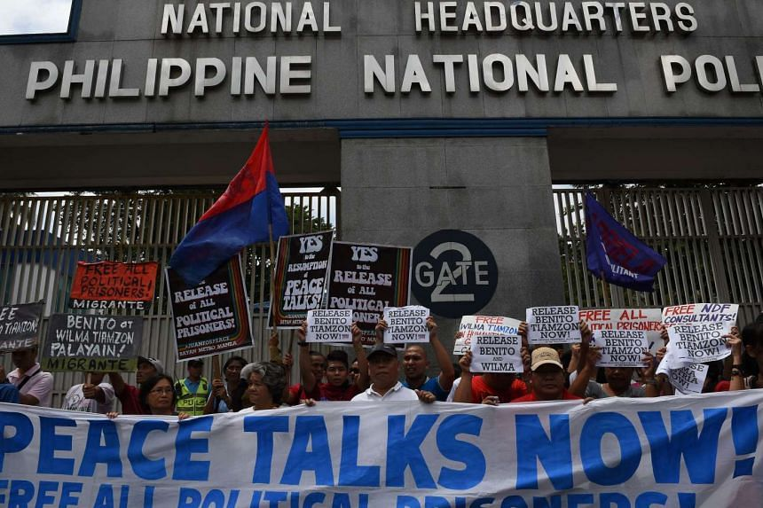 Activists and supporters of communist rebel leaders Benito Tiamzon and his wife Wilma (not pictured) hold a rally outside the gates of the police headquarters in Manila on August 19, 2016.