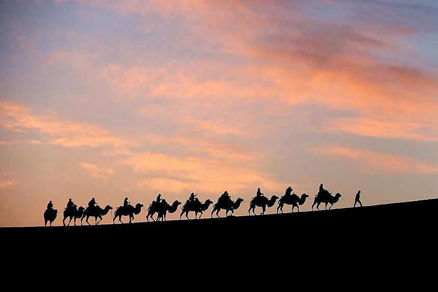 Tourists riding on camels at Yueya Spring in Dunhuang, in China's Gansu province. In the past, Gansu was a key transfer point and trading area along the ancient Silk Road.