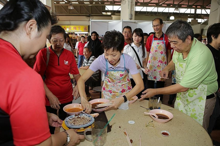 Minister for Culture, Community and Youth Grace Fu lending a hand with cleaning up at Yuhua Village Market and Food Centre as part of an outreach programme to encourage diners to return their trays after meals.