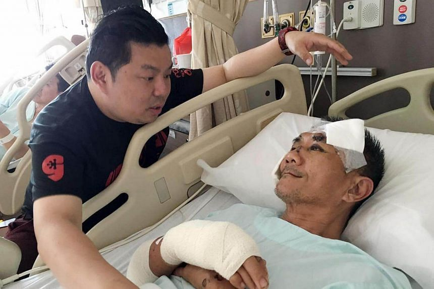 Albert Leow (left), 41, visiting Mr Lim Choon Seng (right), 51, at Tan Tock Seng Hospital on Oct 4, 2016, four days after the accident.