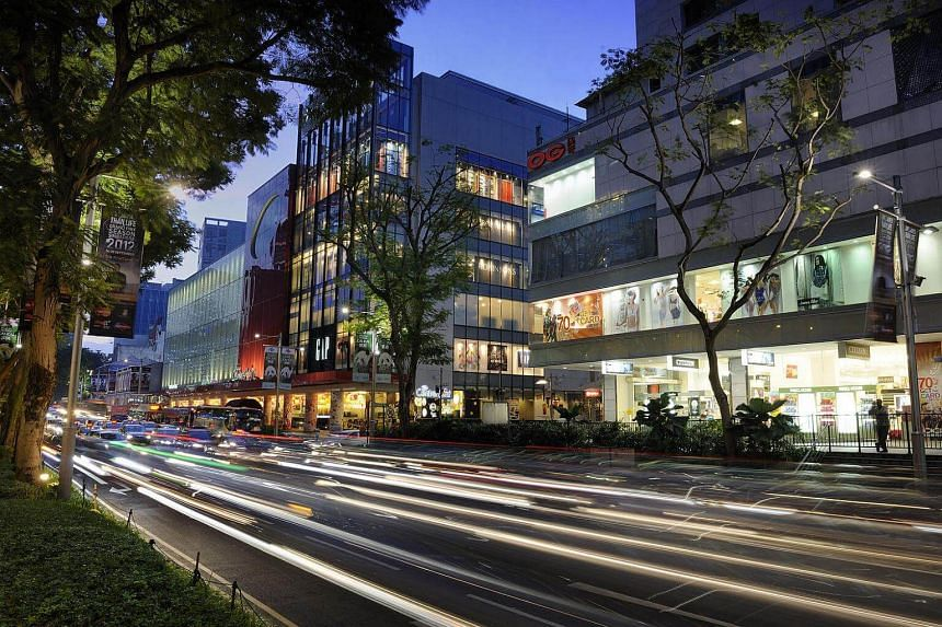 Traffic moves past Frasers Centrepoint's The Centrepoint mall (centre) and OG Pte Ltd's Orchard Point mall (right) in Orchard Road during the evening rush hour.