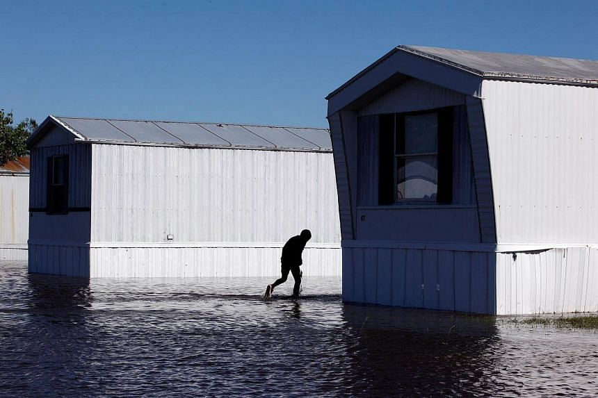 A young resident wades through flood waters at a trailer park after Hurricane Matthew hit Lumberton, North Carolina on Oct 9, 2016.