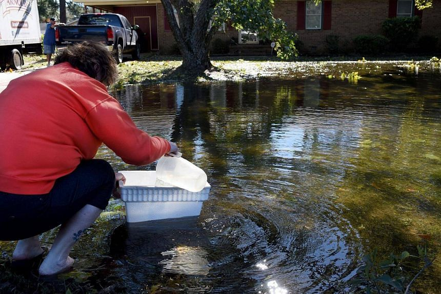 Renee Cameron, front, scoops water out of her front yard for her toilet inside her Hope Mills home as husband, John Cameron watches from afar, following flooding caused by Hurricane Matthew in Fayetteville, North Carolina, US, on Oct 9, 2016.