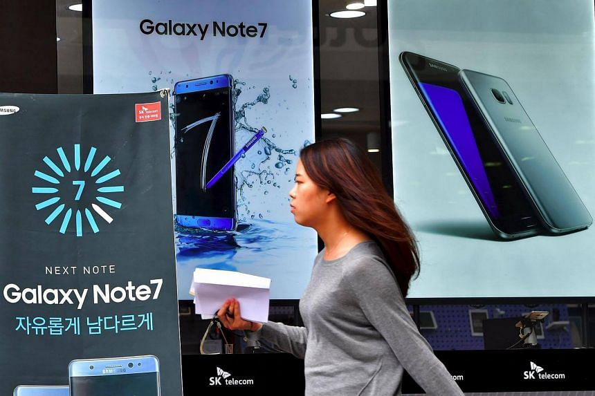 A woman walking past billboards of Samsung Galaxy Note 7 (left) and Galaxy S7 (right) at a mobile phone shop in Seoul on Sept 12, 2016.