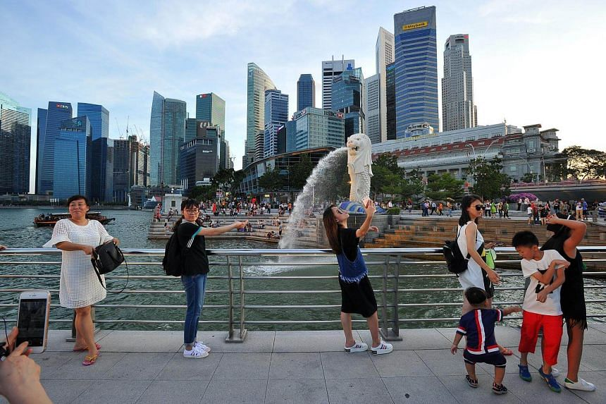 People taking photographs at the Merlion Park with the skyline of Singapore's Central Business District in the background.