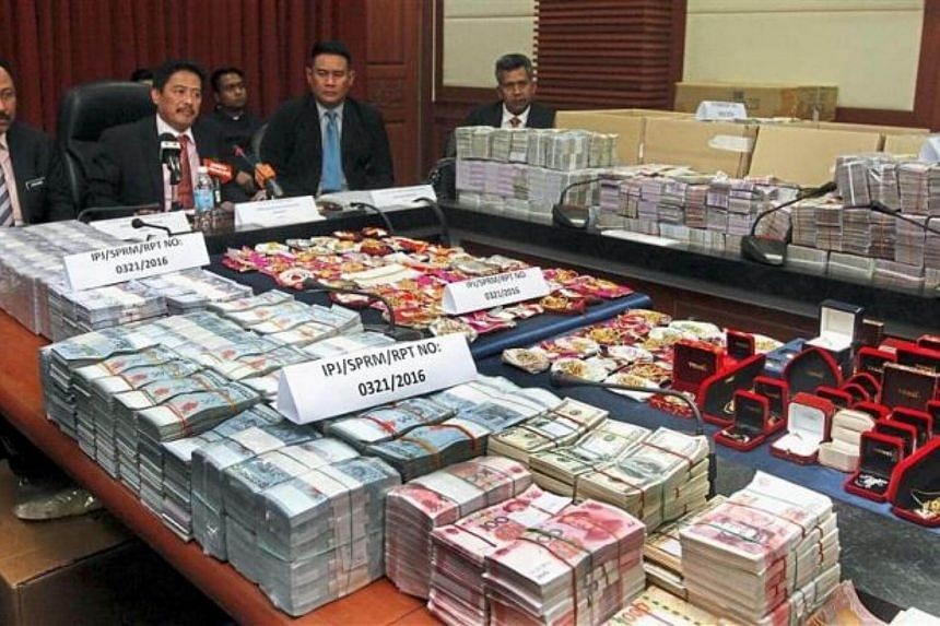 Cash and jewellery seized during the raid were displayed at a press conference in Kota Kinabalu.
