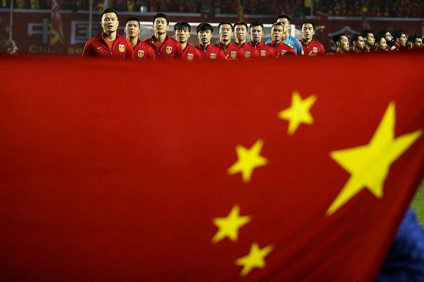 China's football team listens to national anthem behind a Chinese national flag ahead of their 2018 World Cup Qualifying match against Syria.