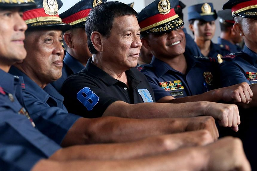 Philippines President Rodrigo Duterte (center) with police officers during his visit to Camp Abendan in Zamboanga City, Philippines, on Oct 10, 2016.
