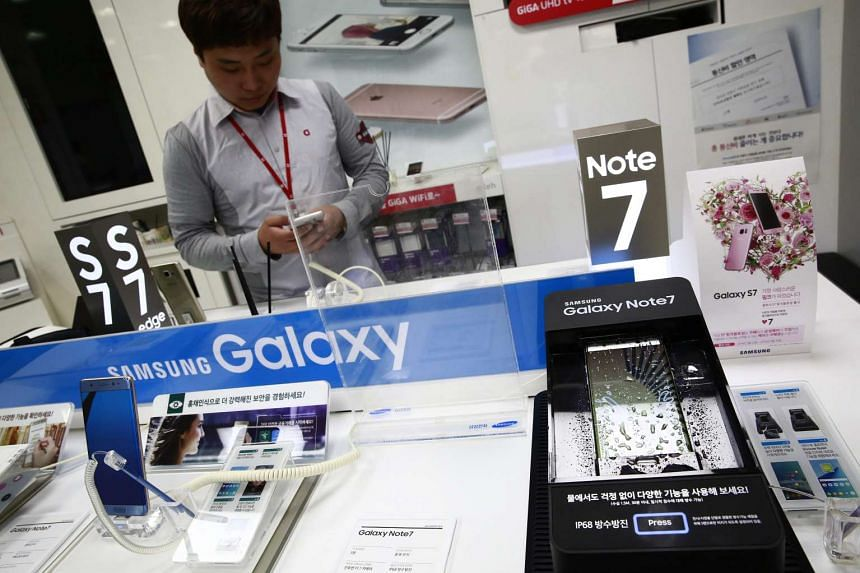 A salesman stands next to the Samsung Galaxy Note7 at a store in Seoul, South Korea, on Oct 11, 2016.