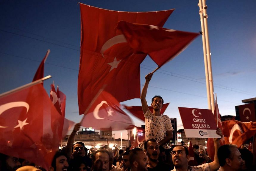 Pro-Erdogan supporters wave national flags as they chant slogans during a rally in Istanbul on July 18, 2016, following the military failed coup attempt of July 15.