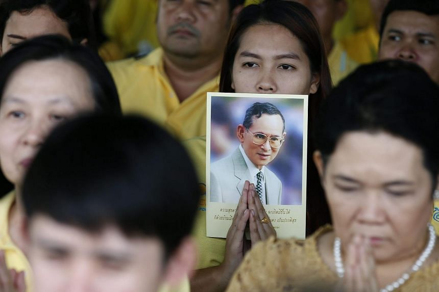 Thai people holding pictures of Thai King Bhumibol Adulyadej as they pray on June 9, 2016, during the celebrations of the monarch's 70th anniversary of accession to the throne.