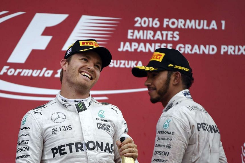 Nico Rosberg (left) celebrates on the podium with third placed Lewis Hamilton, after winning the Japanese Formula One Grand Prix on Oct 9, 2016.