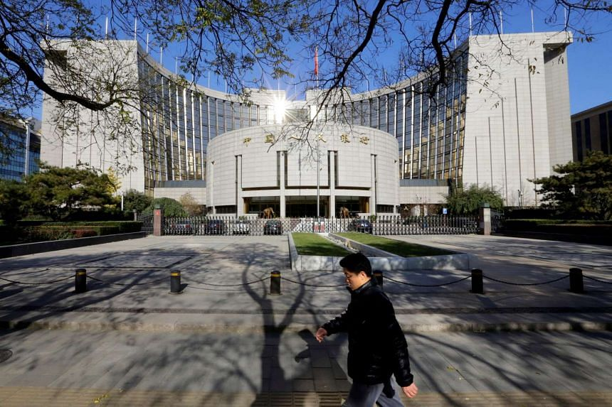 A man walks past the headquarters of the People's Bank of China, the central bank, in Beijing on Nov 20, 2013.