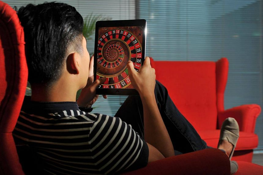 Posed photograph of a man playing online roulette game on his tablet.