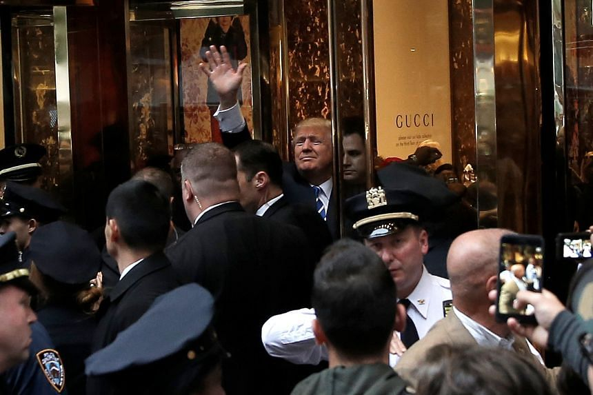 Republican presidential nominee Donald Trump waves to supporters outside the front door of Trump Tower where he lives in the Manhattan borough of New York, US, on Oct 8, 2016.