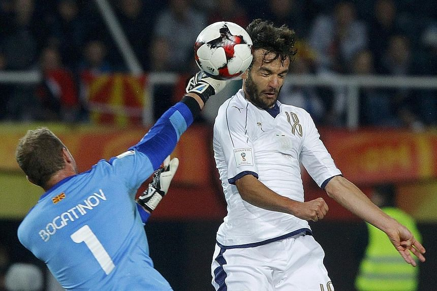 Macedonia goalkeeper Martin Bogatinov being challenged by Italy's Marco Parolo in a World Cup qualifier in Skopje, Macedonia, on Sunday.
