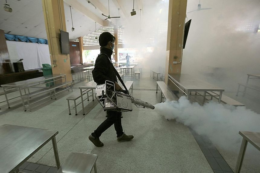 A worker spraying chemicals to kill mosquitoes in the Sathon district of Bangkok. Two Thai babies have been diagnosed with Zika-linked microcephaly.